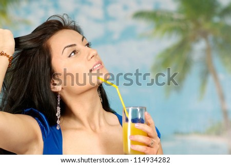portrait of a beautiful young woman with juice on a blue