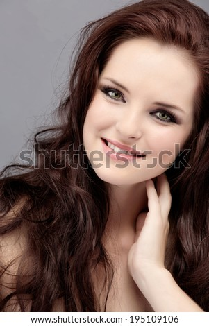 Portrait of a beautiful young woman with long curly hair over grey studio background, wearing natural makeup