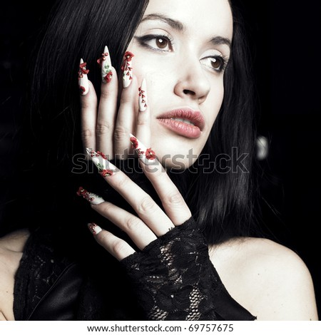 Portrait of a beautiful young woman with long, designer nails - stock photo