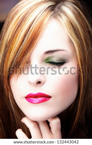 Portrait of a beautiful young woman with long hair wearing fashion makeup of green eyeshadow and pink lipstick