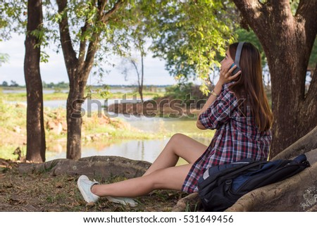 portrait of a beautiful, young woman with music sitting on grass under the tree.