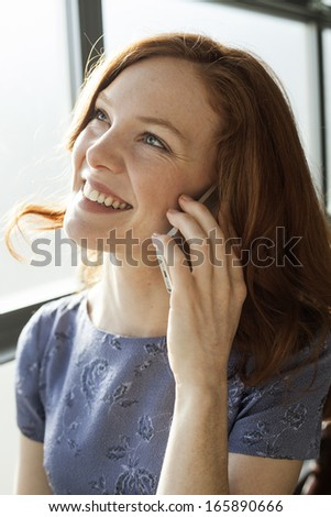 Portrait of a beautiful young woman with red hair and blue eyes talking on a cell phone. - stock photo