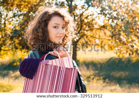 Portrait of a beautiful young woman with shopping bags and autumn background - stock photo