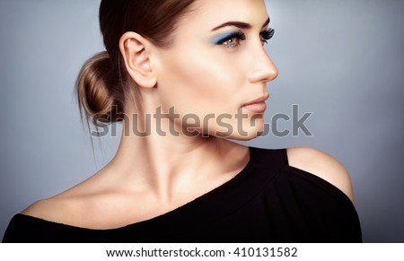 Portrait of a beautiful young woman with stylish makeup over on gray background, profile face, gorgeous fashion look - stock photo