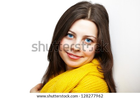 Portrait of a beautiful young woman with yellow scarf leaning against a white wall.