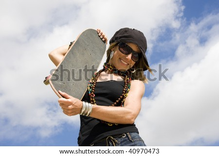 Portrait of a beautiful young women with a skateboard - stock photo