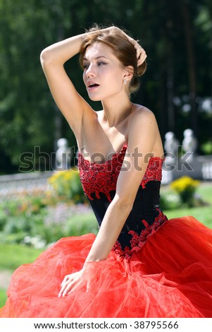Portrait of a beautifull woman in a red dress walking in park