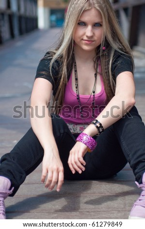 Portrait of a blond girl sitting on a bridge - stock photo