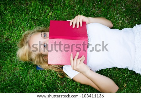 Portrait of a blond girl with a book lying on the grass - stock photo