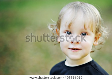 Portrait of a blond-haired, blue-eyed, curly-haired boy blurred background, close-up, copy space. - stock photo