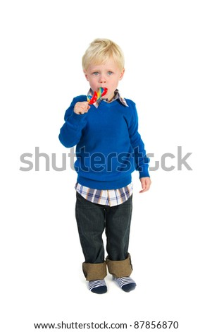 Portrait of a blond toddler eating a colorful lolly
