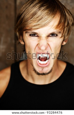 Portrait of a blond vampire, he is looking angrily at the camera. - stock photo