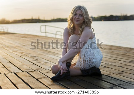 Portrait of a blond woman sitting on a deck wearing white lace dress and short black boots with lake behind her enjoying sun.