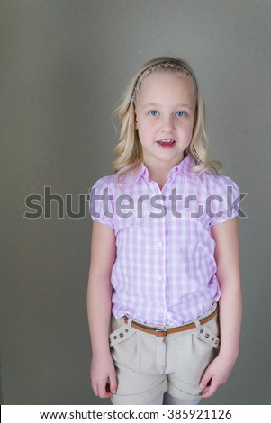 Portrait of a blonde little girl with blue eyes posing