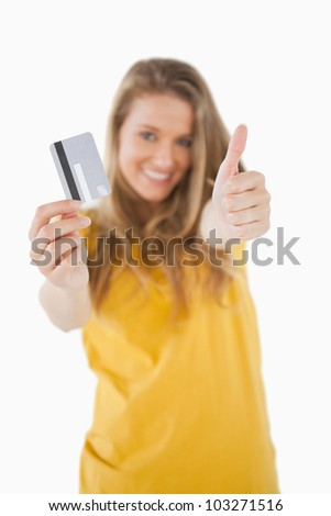 Portrait of a blonde student tending a credit card with the thumb-up against white background - stock photo