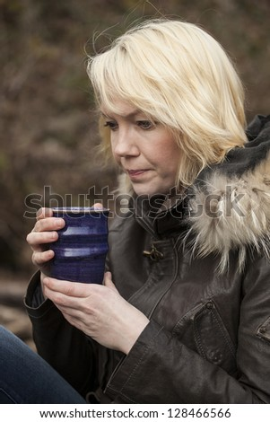 Portrait of a blonde woman holding a cup of coffee. - stock photo