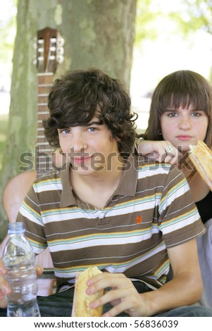 Portrait of a boy and a girl eating sandwiches - stock photo