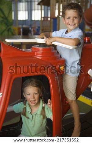 Portrait of a boy and a girl playing with a toy helicopter - stock photo