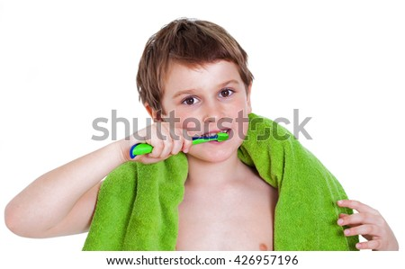 Portrait of a boy brushing teeth, isolated on a white background