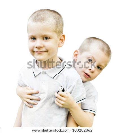 Portrait of a boy embracing his twin brother and both looking at camera with smiles isolated on white. - stock photo