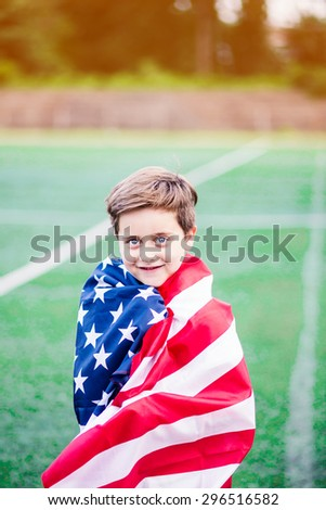 Portrait of a boy holding american flag. Shallow depth of field - stock photo