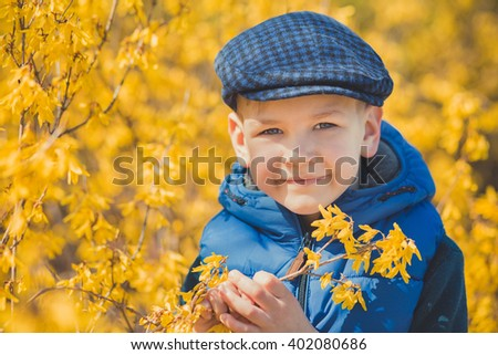 Portrait of a boy in a blue dress on a background of yellow bushes.