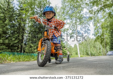 Portrait of a boy in a blue safety helmet on his bike - stock photo