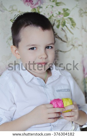 Portrait of a boy in a white shirt, boy pink and yellow thread. Vertical. - stock photo