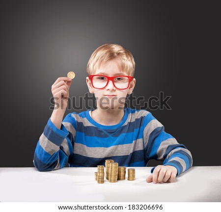 Portrait of a boy in red-framed glasses with a coin in his hand looking at camera - stock photo