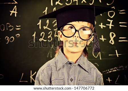 Portrait of a boy in round glasses and academic hat standing near the blackboard in a classroom. - stock photo