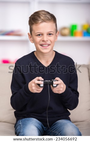 Portrait of a boy is playing computer console. - stock photo