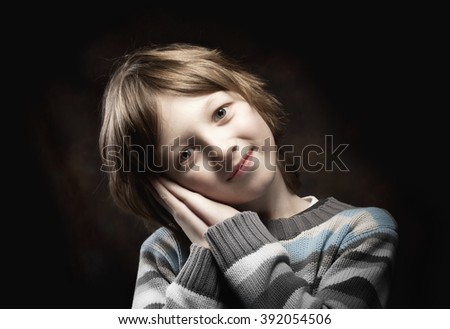 Portrait of a Boy Leaning his Head on his Hands - stock photo