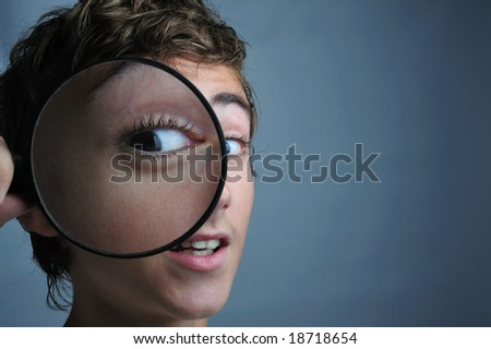 Portrait of a boy looking through a magnifying glass - stock photo