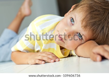 Portrait of a boy lying on the floor of the house