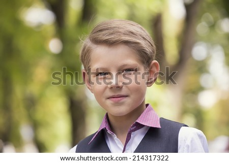 Portrait of a boy on a background of green nature