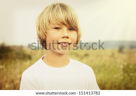 Portrait of a boy on a summer field. - stock photo