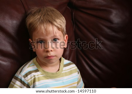 Portrait of a boy on brown leather coach - stock photo