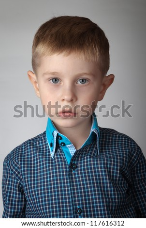 Portrait of a boy on gray background