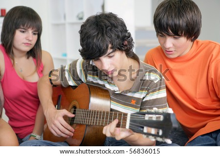 Portrait of a boy playing guitar in front of his friends - stock photo