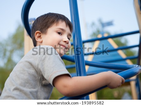 Portrait of a boy playing on the playground - stock photo