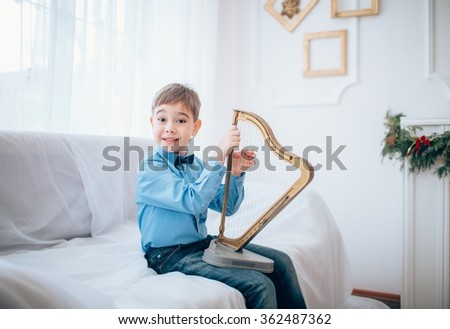 portrait of a boy plays the harp - stock photo