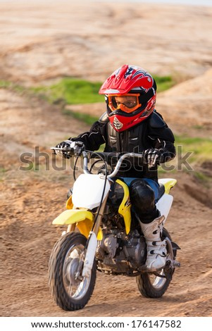 Portrait of a boy racer on a motorcycle in the desert - stock photo