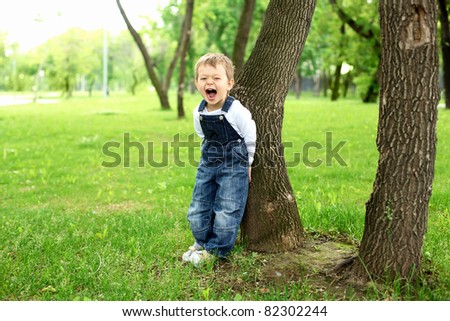 Portrait of a boy standing near the tree in the park - stock photo