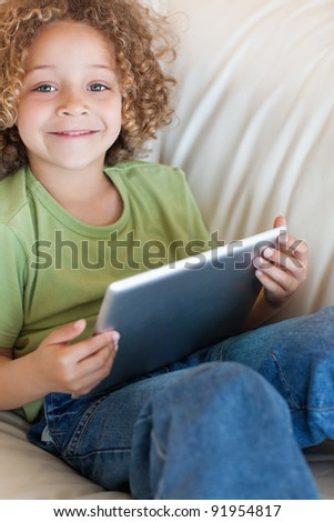 Portrait of a boy using a tablet computer in a living room - stock photo