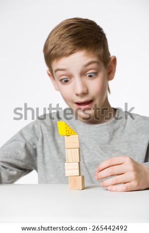 Portrait of a boy watching house made of wooden blocks fall - stock photo