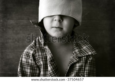 portrait of a boy wearing a hat with eyes closed - stock photo