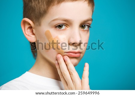 Portrait of a boy with adhesive plaster on his cheek - stock photo