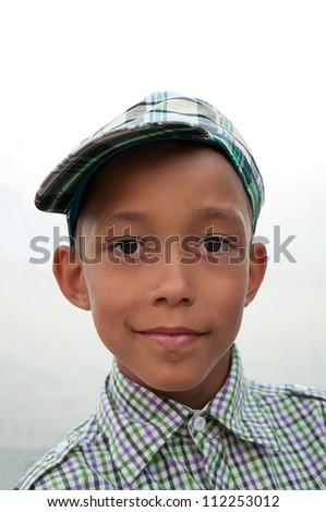 portrait of a boy with brown eyes in cap and shirt - stock photo