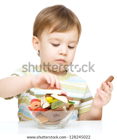 Portrait of a boy with candies, isolated over white - stock photo