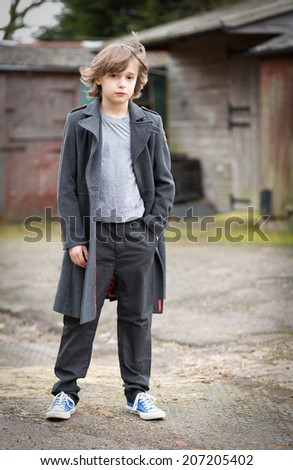 Portrait of a boy with long hair in a long coat standing isolated in a farm yard in front of stables hair blowing in the wind